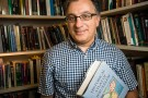 Awad Halabi in front of bookshelf